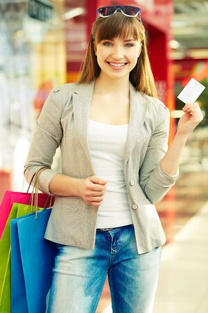shopaholism: Pretty lady with colorful shopping bags showing credit card