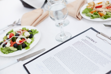 business dinner: Close-up image of a served lunch with a business contract in the foreground