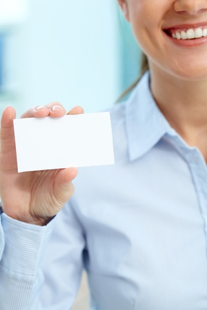 Vertical image of a business woman showing a blank card photo