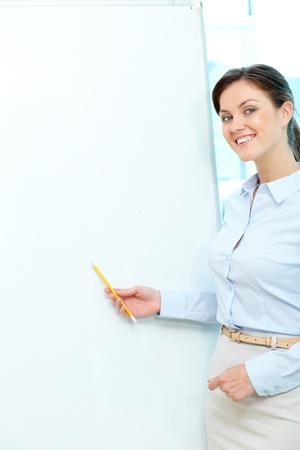 lecturing: Vertical portrait of a smiling teacher pointing at a blank whiteboard