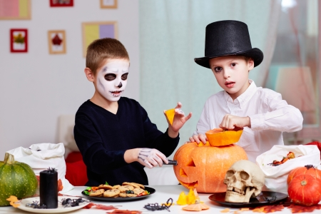 antichrist: Photo of two eerie boys cutting holes in pumpkins at Halloween table  Stock Photo