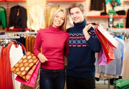 Portrait of amorous couple with paperbags looking at camera with smiles photo