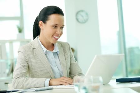 Portrait of pretty secretary networking in office photo