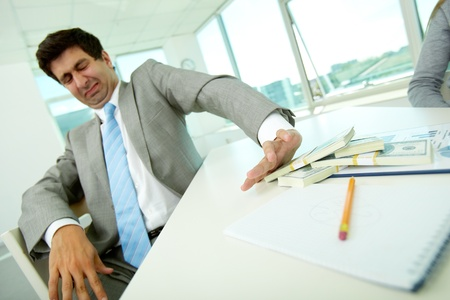 offense: Image of disgusted male employee moving dollar bills away and refusing to take bribe Stock Photo