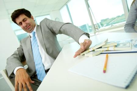 delito: Imagen de sexo masculino de disgusto moviendo billetes de un d?lar de distancia y se niega a tomar soborno Foto de archivo