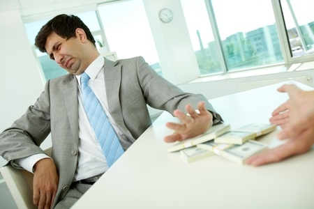 push people: Image of disgusted male employee moving dollar bills away and refusing to take bribe Stock Photo