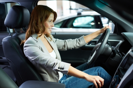 Cheerful young woman learning to drive on her own photo