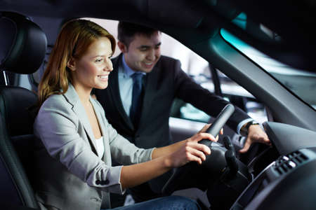 consulted: Photo of young woman sitting in car while being consulted by salesman in automobile center Stock Photo