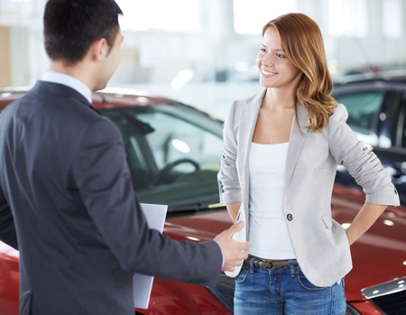 Successful young lady discussing her potential purchase with a car dealer photo
