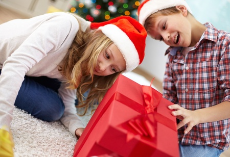 Portrait of happy siblings looking inside big red giftbox on Christmas evening Stock Photo