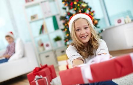 generoso: Retrato de ni?a alegre con caja de regalo rojo mirando a la c?mara en la noche de Navidad Foto de archivo