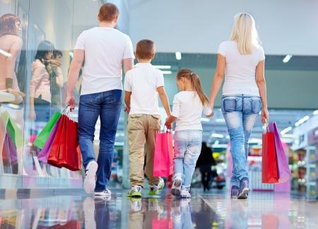 購入を運ぶショッピング家族の後姿 写真素材