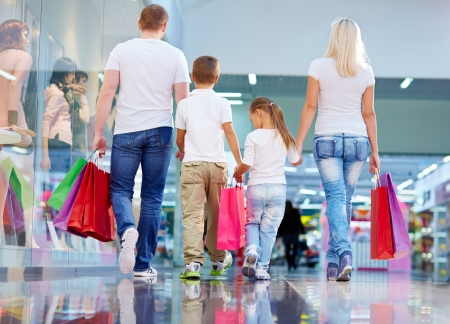 Rear-view of shopping family carrying purchases Imagens