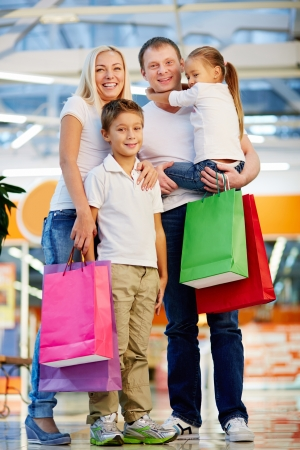 shoppingbags: Vertical portrait of a cheerful family standing together holding shopping-bags Stock Photo