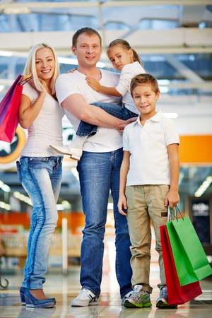 Vertical portrait of a family of four enjoying doing shopping photo
