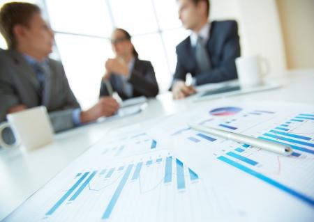 Close-up van zakelijke documenten op het bureau lag, kantoormedewerkers bijeen in de achtergrond
