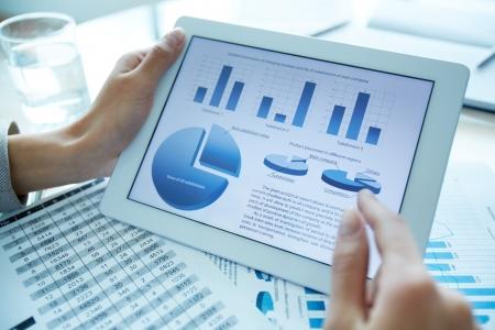 デジタル タブレットの統計データを保持している金融アナライザーのクローズ アップ 写真素材