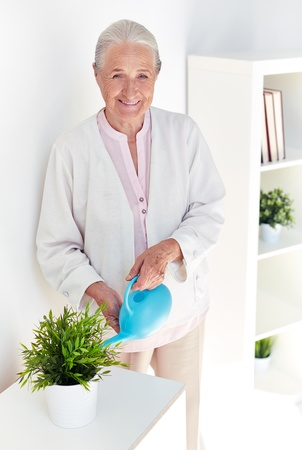 Portrait of elderly female watering flowers at home photo