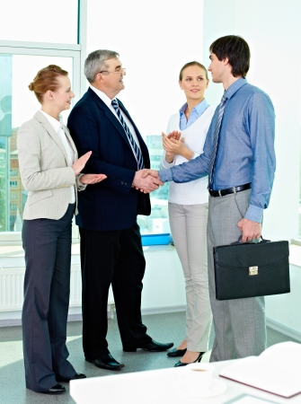 Photo of successful businessmen handshaking after striking deal with applauding women near by photo