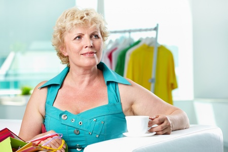 Portrait of middle aged woman with cup of coffee after shopping photo