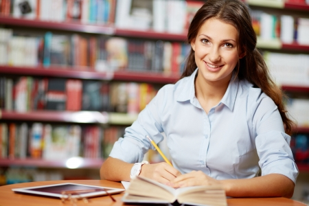 student girl: Portrait of pretty student looking at camera while working in college library Stock Photo