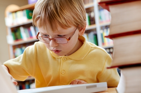 Portrait of serious schoolkid working with laptop in the library Stock Photo