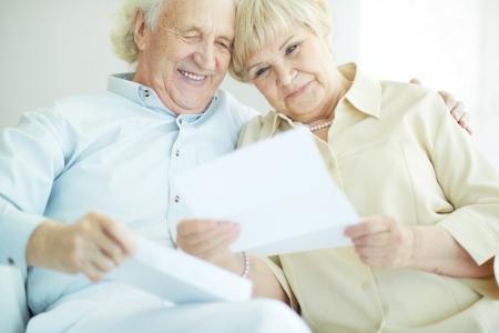 Portrait of happy senior couple reading letter together Stock Photo - 22028976