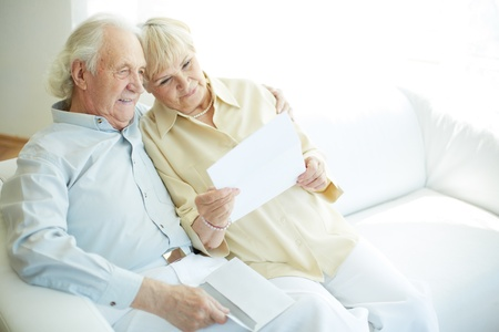 retirement  age: Portrait of a candid senior couple sitting and reading letter