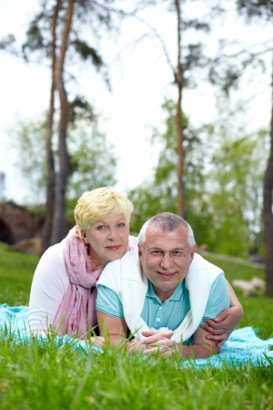 Happy mature couple lying on grass and looking at camera in the countryside photo
