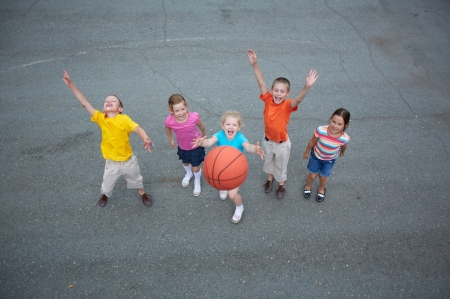 kids playing outside: Image of happy friends playing basketball on sports ground Stock Photo