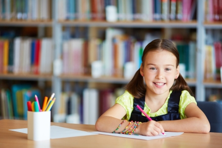 Portrait of a lovely girl drawing with pencil in library photo