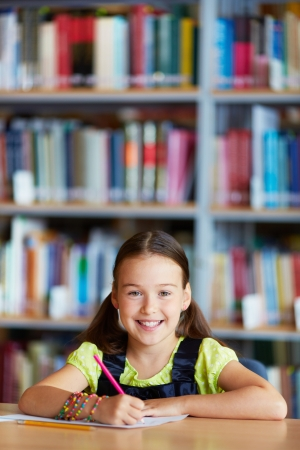 Portrait of a lovely girl drawing with pencil in library Stock Photo - 22129142