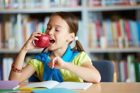 Portret van gezonde schoolmeisje eten van grote rode appel Stockfoto