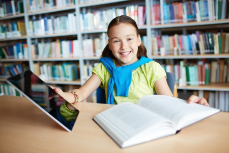Portrait of a lovely girl with touchpad and open book sitting in library photo