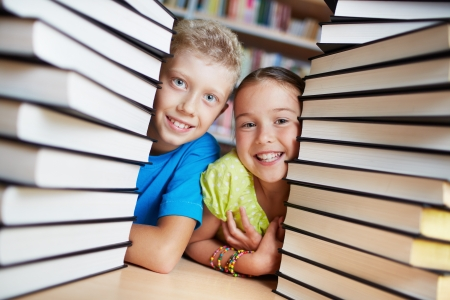 Portrait of happy schoolkids between stacks of books looking at camera Stok Fotoğraf