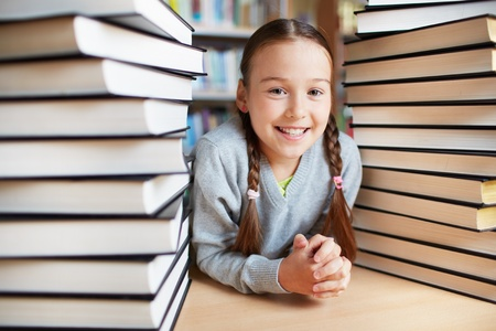 Portrait of happy schoolkid looking at camera surrounded by two stacks of books photo