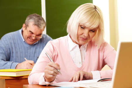 making notes: Portrait of mature female making notes in copybook with senior man on background
