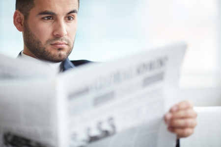 reading news: A young serious businessman reading newspaper