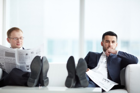 interested: A young serious businessman with newspaper looking at camera with his colleague reading news near by