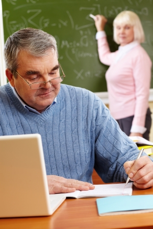 pensionary: Portrait of mature man making notes on background of teacher standing by blackboard