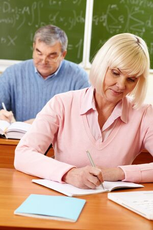 pensionary: Portrait of mature female making notes in copybook with senior man on background