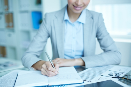financial planner: Office lady writing down a week plan in her organizer Stock Photo