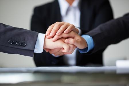 交際および結束を象徴する互いの上に手をビジネス パートナーのイメージ 写真素材