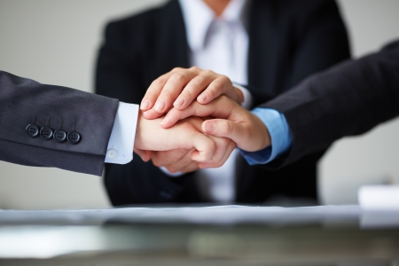 companionship: Image of business partners hands on top of each other symbolizing companionship and unity