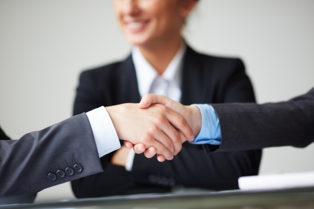 associates: Image of business partners handshaking on background of businesswoman