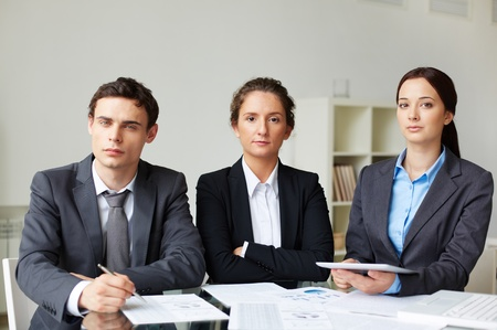 Portrait of smart business partners looking at camera at workplace photo