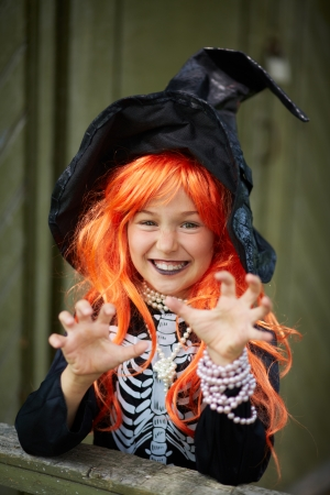 antichrist: Portrait of Halloween girl with red hair wearing black hat