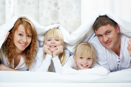 Portret van vrolijke familie met een tweeling liggen onder deken Stockfoto