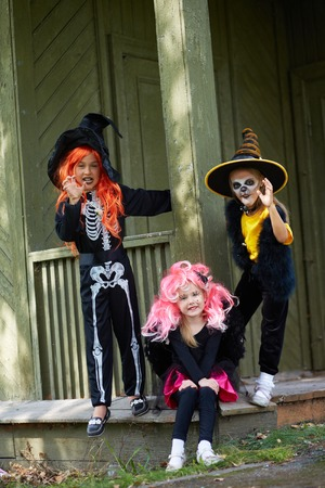 antichrist: Portrait of three Halloween girls looking at camera on the porch of dilapidated house Stock Photo