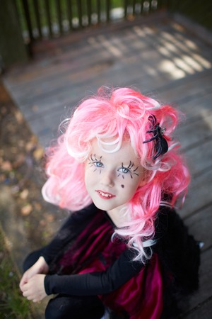 antichrist: Portrait of cute girl in Halloween costume and pink wig looking at camera Stock Photo